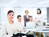 Group of five young business people working at office with businesswoman sitting in front. poster