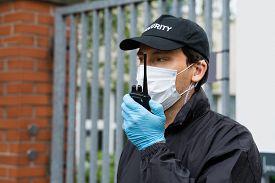 Security Guard In Face Mask Talking On Walkie Talkie