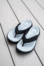 Black Flip Flops On Gray Deck Background