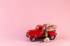 Bouquet Of Dried Roses In The Back Of A Toy Truck. Free Space To Place Text. The Concept Of Holiday