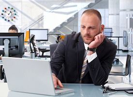 Confident caucasian stock broker working at bright financial business office desk with laptop computer. Determined, suit.