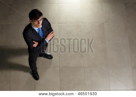 Image of young businessman in glasses arms crossed. Top view