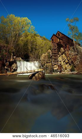 Old wooden building standing on top of a cliff close to a river waterfall in Crystal Mill Ghost town, Colorado, USA