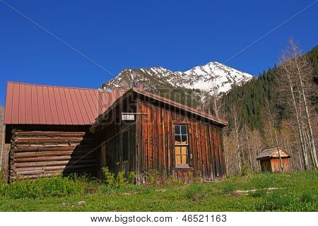 Old wooden buildings in the Crystal Mill Ghost Town on a bright sunny day with a snow capped mountain in the background. Colorado, USA