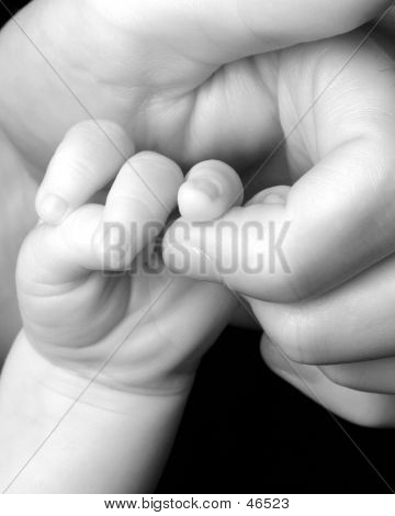 Newborn grasping the finger of a parent poster