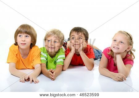 cute children in colored t-shirts lying and smiling looking with interest up in left corner, over white background