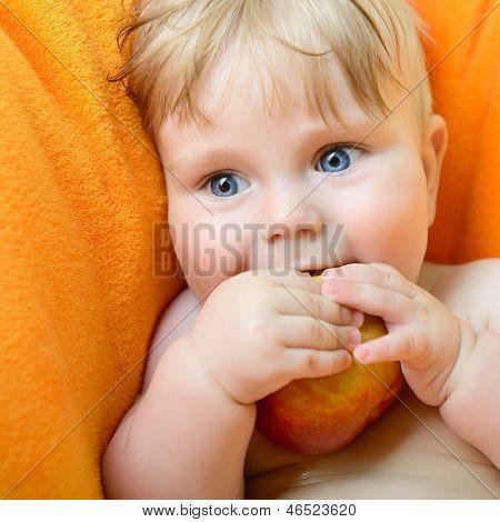 Little baby boy portrait eating red apple