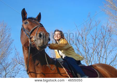 Young woman riding on big brown horse poster