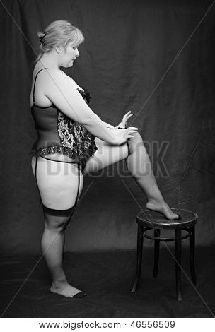 Vintage style picture of an overweight woman dressed in black lingerie posing on a black background.