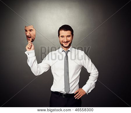 cheerful man hiding behind angry mask over dark background