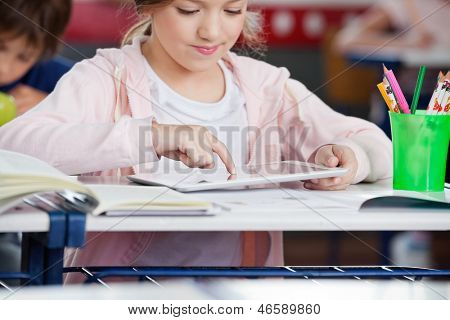 Little schoolgirl using digital tablet at desk in classroom