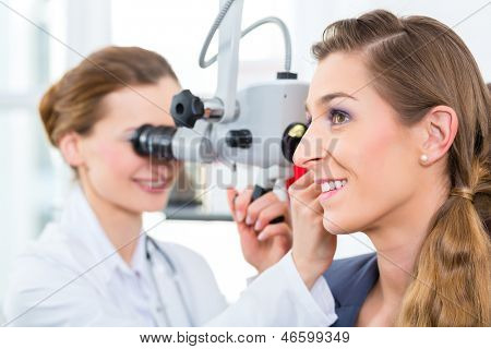 Doctor - Young female doctor or ENT specialist - with a patient in her practice, examining the ear with a endoscope