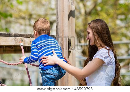 Family - Mother and son playing on a jungle gym