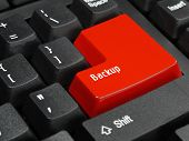 Closeup of computer keyboard key in red color spelling Backup poster
