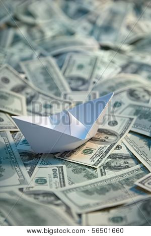 Origami paper ship at sea of money