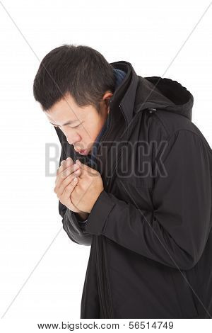 Young Man Blowing To Warm Hands In Cold Day