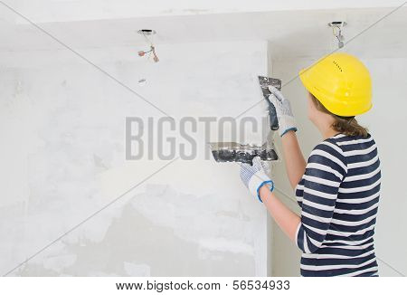 Female Plasterer Repairs Wall With Spackling Paste. Space For Your Text.