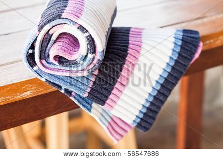 Knit Striped Scarf On Wood Table
