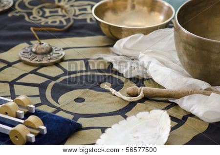 A table-top arrangement around a ying yang of tibetan healing instruments used for holistic healing. poster