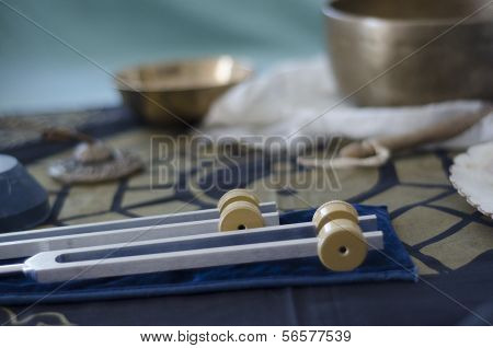 A wo healing tuning forks with Tibetan singing bowls and tingsha in the background. poster