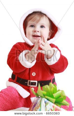 Little Happy Girl In Red Santa's Clothes Clapping In Her Hands