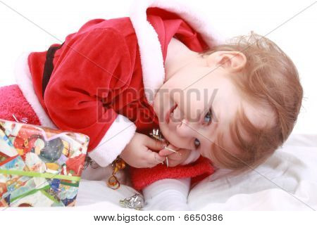 Little Happy Girl In Red Santa's Clothes With Present