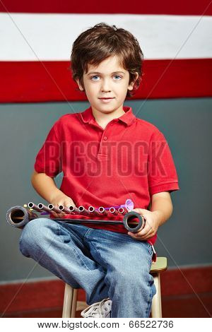 Boy playing xylophone in music class in elementary school
