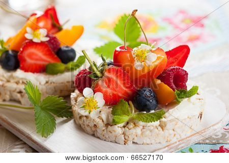 Multigrain rice cakes with berries, fruit and soft cheese for healthy breakfast