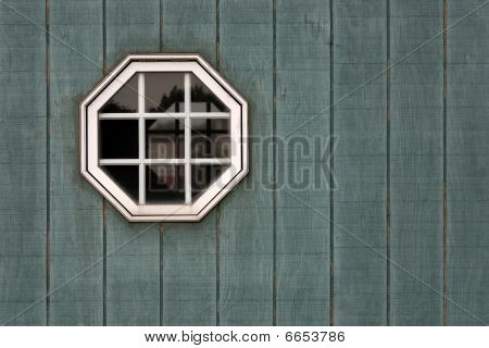 Octagon window on green wood
