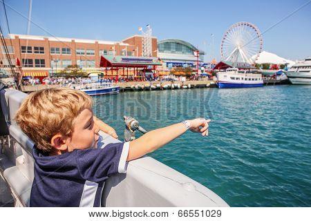 Boy on a  boat pointing (focus on boys arm)