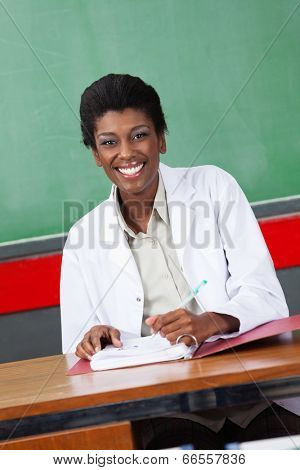 Portrait of happy African American female teacher with pen and binder sitting at desk in classroom