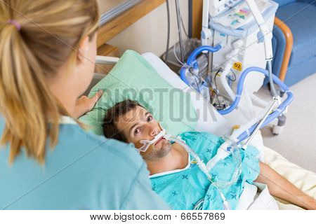 High angle view of patient looking at nurse as she adjusts his pillow in hospital room