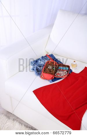 Handbag with accessorises, female clothes and perfumes in bottles on sofa on  home interior background
