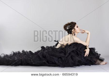 Beautiful young woman in luxurious long black dress.