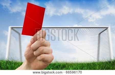 Hand holding up red card against goalpost on grass under blue sky