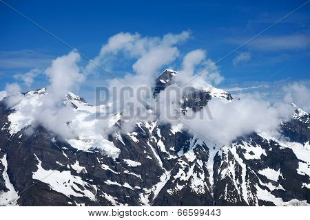 Alps in Austria mountain peak in Hohe Tauern with snow and clouds poster