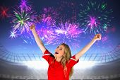 Cheering football fan in red against fireworks exploding over football stadium poster