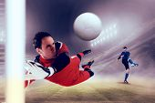 Fit goal keeper jumping up against football stadium poster