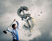 Young businessman crashing with hammer stone dollar symbol poster