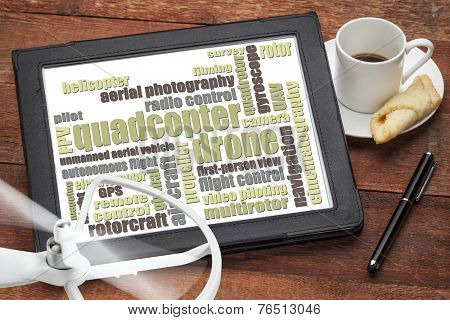 quadcopter drone word cloud on a digital tablet with a cup of coffee and rotating drone propeller