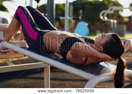 fitness woman doing situps in outdoor gym woking out strength training