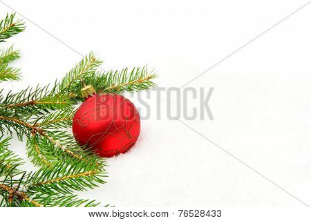 Red Christmas Bauble With Red Star And Needles Fir On Snow