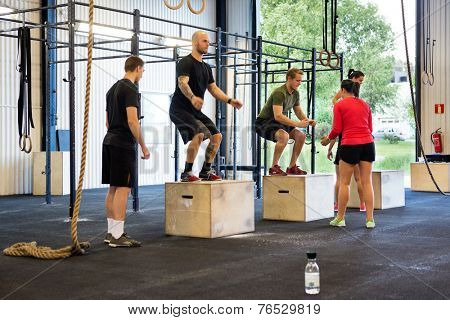 Group of athletes practicing box jumps at gym