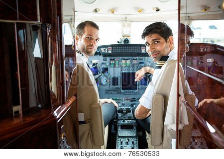 Portrait of confident pilots in corporate plane cockpit