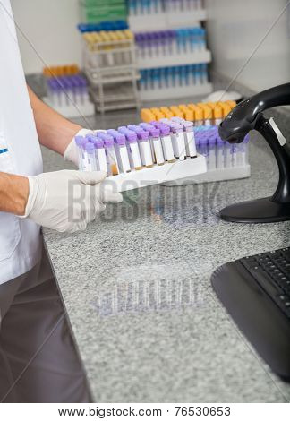 Cropped image of male technician holding test tube holder in medical laboratory