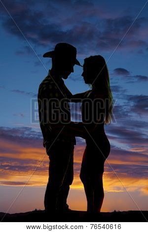 Silhouette Of Cowboy And Woman Arms Around Each Other