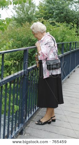A happy 85 year old senior lady on a Sunday afternoon stroll in the park looking at a river from a bridge poster