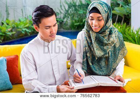 Asian Muslim man teaching woman reading Koran or Quran in living room