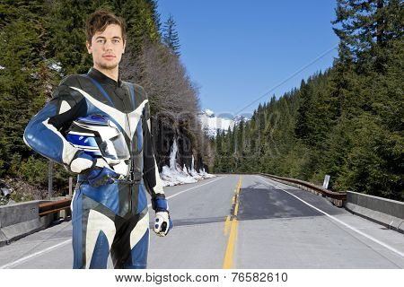 Motor cyclist posing with his helmet under his arm on a beautiful mountain road in early spring
