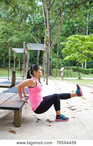 Sporty woman doing dips on right leg in outdoor exercise park
